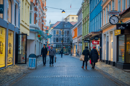 BERGEN, NORWAY - APRIL 03, 2018: Unidentified people walking in a quiet side street citys well-preserved 19th century architecture, on a typically cloudy day