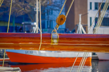 Close up of selective focus of ropes around mast support boom on boat in port of Alesund in Norway