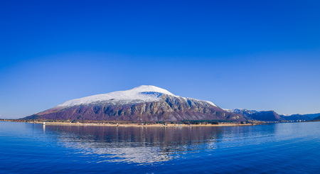 Outdoor view of mountain range in Norway. The beautiful mountain covered partial with snow in Hurtigruten region in Norway. Stock Photo