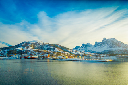 Beautiful outdoor view of some buildings in a coast on Hurtigruten voyage, during a blue sky in Norway.