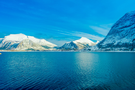 Amazing landscape of coastal scenes of huge mountain covered with snow on Hurtigruten during voyage in a blue sky