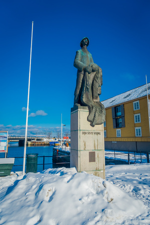 TRONDHEIM, NORWAY - APRIL 04, 2018: View of the Last Viking Statue, silhouetted against blue sky. Bronze figure with stands in the port