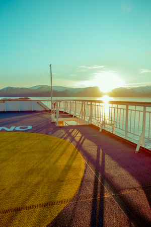 ALESUND, NORWAY - APRIL 04, 2018: Outdoor view of Hurtigruten voyage in cruise along Norwegian coast during a heavy sun shine Editorial