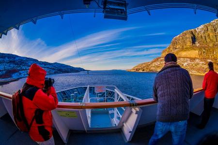 ALESUND, NORWAY - APRIL 09, 2018: Outdoor view of unidentified people taking pictures at frontside of the ship cruise in Hurtigruten