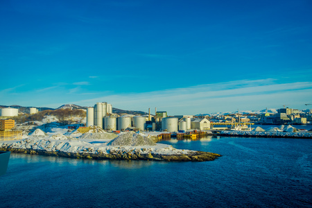 Outdoor view of industrial port area, showing ships and herring oil production plant during a winter season and blue sky, in port of Bodo, Norway
