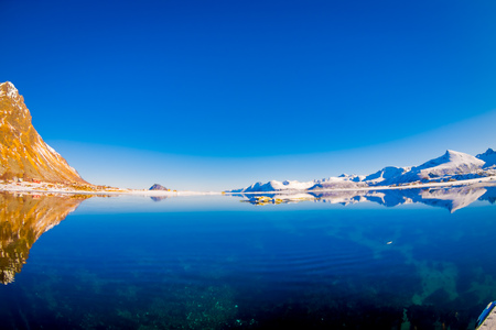 Scenic view of fjord with yellow mountain peaks and reflection in water on Lofoten islands in Norway, Scandinavia, Europe