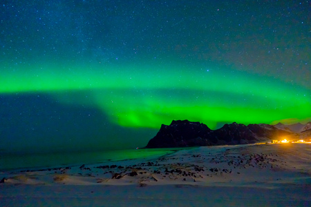 Beautiful picture of massive green vibrant Aurora Borealis, also know as Northern Lights in the night sky over Lofoten Islands