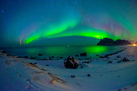 Beautiful picture of massive multicoloured vibrant Aurora Borealis, Aurora Polaris, also know as Northern Lights in the night blue sky over Lofoten Islands Stock Photo