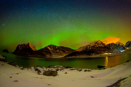 Beautiful outdoor view of massive vibrant Aurora Borealis or Aurora Polaris, in the night sky with long exposure effect over Lofoten Islands