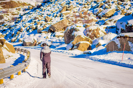 Outdoor view of frozen street with unidentified man walking in the road, covered with snow during a winter season in Skjelfjord in Lofoten Islands