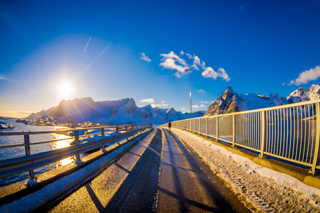 Outdoor view of frozen street with blurred unidentified woman walking in the road, covered with snow during a winter season with a sun shinne in Skjelfjord in Lofoten Islands