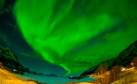 Northern lights shine bright and beautiful above sharp peaks and lakes of Lofoten mountains