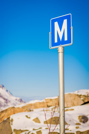 Outdoor view of metallic sign with the letter M, at outdoors in the streets during a winter season in Skjelfjord in Lofoten Islands Stock Photo