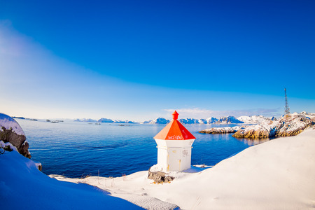 HAMMNOY, LOFOTEN, NORWAY, APRIL, 10, 2018: Outdoor view of white stoned structure with red rooftop in the border and land covered with snow with blue lake in snowy winter in the Arctic Circle Редакционное