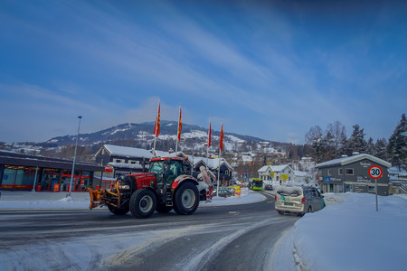 GOL, NORWAY, APRIL, 02, 2018: Outdoor view of heavy red machinery cleaning the snow after a winterstorm covered with snow in GOL