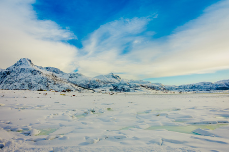 Beautiful outdoor view of white snow covered the land with frozen lake and huge mountains behind in winter in the Arctic Circle in lofoten island