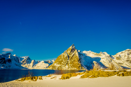 Outdoor view of mountain peaks covered with snow during winter in gorgeous blue sky Olenilsoya in Reine, Lofoten Islands, Norway