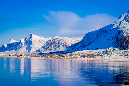 Outdoor view of buildings in the seaside with a huge mountain behind in Svolvaer, starting point for held yearly in March International cod fishing competition