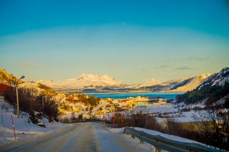 Outdoor view of frozen street in Skjelfjord with a town in the horizont in Lofoten Islands
