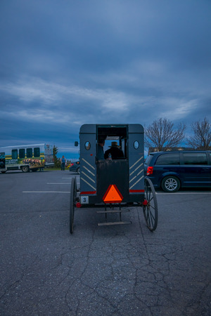 Pennsylvania, USA, APRIL, 18, 2018: Outdoor view of the back of an old fashioned, Amish buggy with people inside and a horse riding on gravel rural road