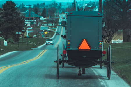 Pennsylvania, USA, APRIL, 18, 2018: View of the back of an old fashioned, Amish buggy with a horse riding on gravel rural road