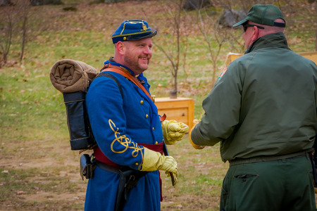 MOORPARK, USA - APRIL, 18, 2018: Man with blue uniform, backpack and holding a sword talking with other man with green uniform representing the Civil War Reenactment in Moorpark Editorial