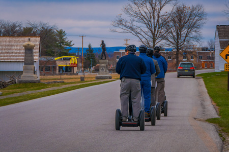 GETTYSBURG, USA - APRIL, 18, 2018: Back view line of tourists on Segways Seg Tours in Gettysburg National Military Park, in a tour on Cemetery battlefield park
