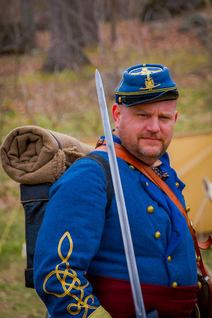 MOORPARK, USA - APRIL, 18, 2018: Unidentified man wearing blue uniform, backpack and holding a sword, representing the Civil War Reenactment in Moorpark Editorial