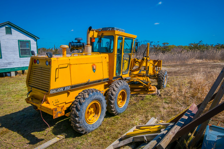 LONG ISLAND, USA, APRIL, 04, 2018: Outdoor view of huge yellow heavy machinery parked at outdoors close to a wooden house building at Long island Imagens - 120102492