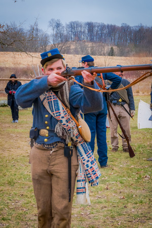 MOORPARK, USA - APRIL, 18, 2018: Close up of pretty boy holding a gun in his hands ready to shoot representing the civil War Reenactment in Moorpark, the largest battle reenactment Editorial