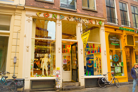 AMSTERDAM, NETHERLANDS, APRIL, 23 2018: Outdoor view of street full of commercial buildings, with restaurants, salons and jewelry stores in a cloudy day