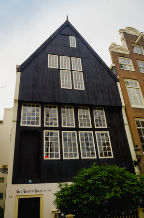AMSTERDAM, NETHERLANDS, APRIL, 23 2018:Outdoor view of black wooden house in the begijnhof dowtown Éditoriale