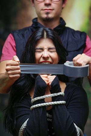 彼女の手をロープで縛られたテープで女性の口を覆う男のクローズアップ。家庭内暴力や誘拐の概念