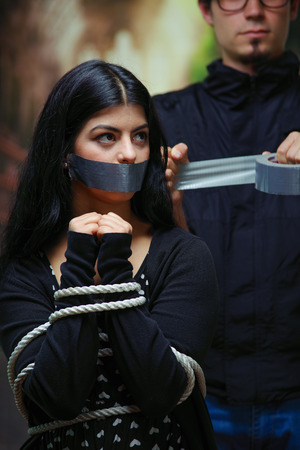Close up of a mans covering a womans mouth with tape, tied with rope her hands. Concept of domestic violence or kidnapping Stock Photo