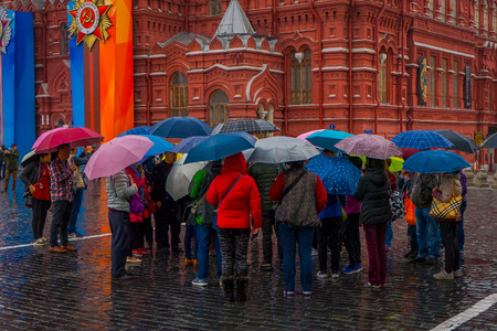 MOSCOS, RUSSIA- APRIL, 24, 2018: Outdoor view of unidentified people with umbrellas protecting from rain walking close to the State Historical Museum on red square in Moscow