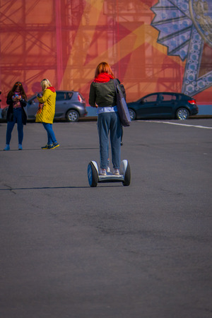 ST. PETERSBURG, RUSSIA, 02 MAY 2018: Outdoor view of unidentified woman using a segway in the streets of the city of st. Petersburg Redakční