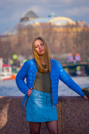 ST. PETERSBURG, RUSSIA, 01 MAY 2018: Blonde russian woman wearing blue jacket and blue skirt, posing for a picture, with blurred background of the city in the horizont in St. Petersburg