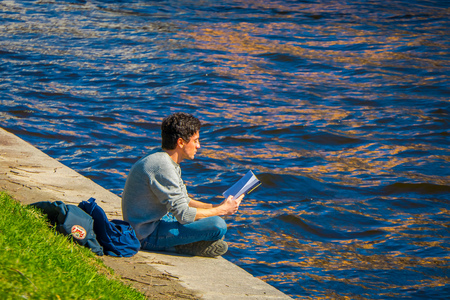 ST. PETERSBURG, RUSSIA, 02 MAY 2018: Unidentified man sitting in the border of the Moika river reading a book and enjoying the gorgeous sunny day in St Petersburg