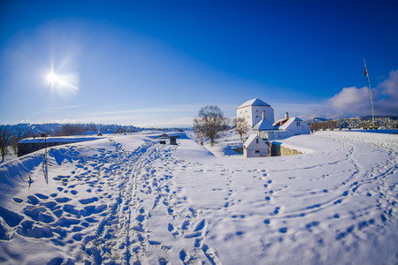Sunny outdoor view of buildings covered with snow during winter at the norwegian city Trondheim in the horizont Stock Photo