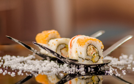 Close up of delicious sushi rolls over a metallic spoon with small grains of salt served on black table