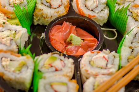 Close up of selective focus of large set of delicious japanese sushi rolls on a black plastic plate
