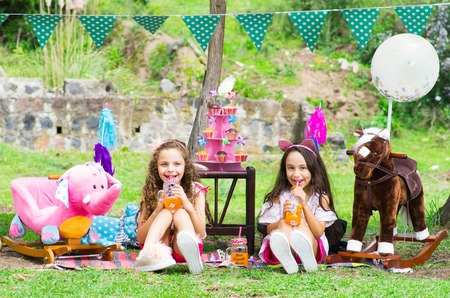 Two little girls drinking juice in a cristal flask at outdoors sitting in a garden on sunny summer day wearing pastel color clothes