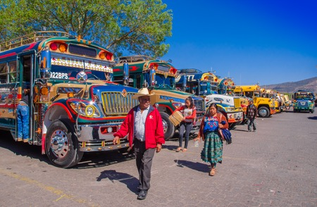 Ciudad de Guatemala, Guatemala, April, 25, 2018: Unidentified people walking in front of guatemalan chicken bus in Antigua, its a name for colorful, modified and decorated bus