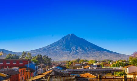 Bella vista esterna dei tetti dell'edificio nella città di Antigua con la montagna del vulcano agua dietro in una bella giornata di sole e cielo blu