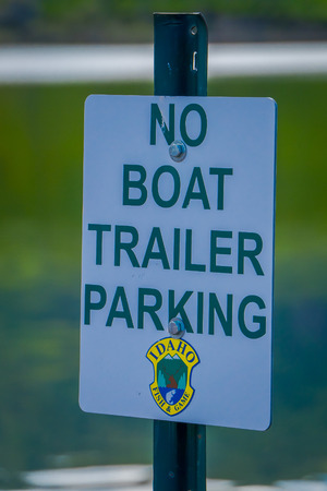 Idaho, USA, June 23, 2018: Close up of informative sign of no boat trailer parking over white metallic structure and blurred lake background behind in Idaho lake in gorgeous sunny day Sajtókép