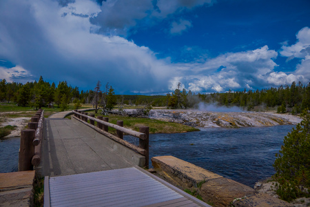 Beautiful outdoor view of wooden bridge over firehole river in the Yellowstone national park in a gorgeous sunny day and blue sky and some clouds in Usa.