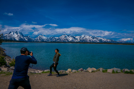 YELLOWSTONE, MONTANA, USA MAY 24, 2018: Outdoor view of unidentified woman posing for a picture in front of Jackson Lake in Grand Teton National Park, Wyoming, Yellowstone