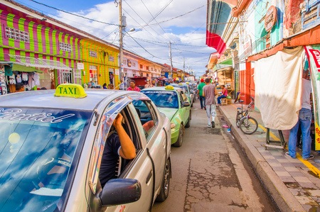 GRANADA, NICARAGUA, MAY, 14, 2018: Cars waiting in the traffic while unidentified people is walking in the street of market stalls at a colorful street in Granada Editorial