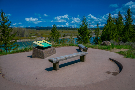 YELLOWSTONE, MONTANA, USA MAY 24, 2018: Beautiful outdoor view of informative sign and wooden public chair with a view of Jackson Lake Dam in Grand Teton National Park