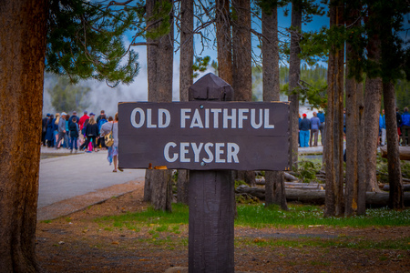 YELLOWSTONE, MONTANA, USA MAY 24, 2018: Close up of informative sign of old faithful geyser written over a wooden structure of the Old Faithful erupting in Yellowstone National Park